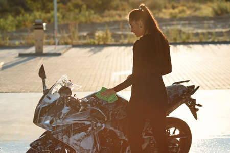 Seductive young woman washing stylish sport motorcycle and wipes it from purple foam. Taking care about vehicle.