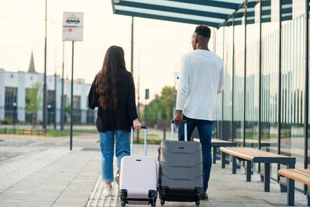 Stylish multiracial couple carrying their suitcases on wheels going to the airport direction.