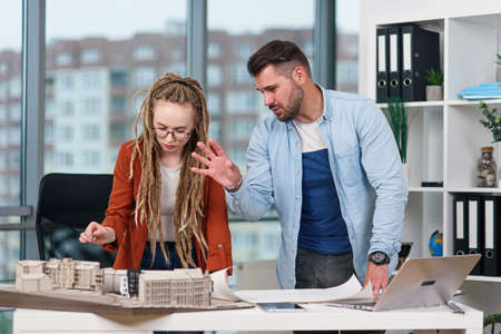 High-skilled hardworking creative male and female designers working with mock-up of future buildings Stock Photo