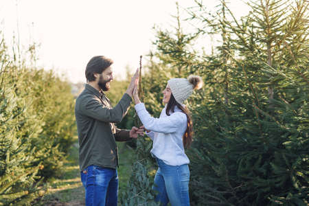 Good-looking stylish smiling young couple ties with threads beautiful christmas tree and giving high five.