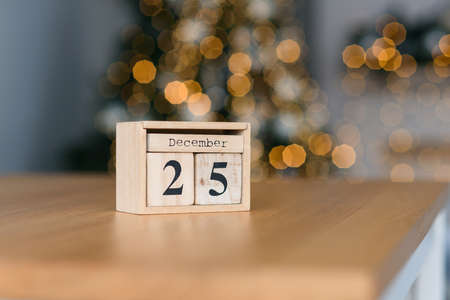 Wooden blocks calendar with the date of December 25 on the Christmas lights bokeh background. 免版税图像