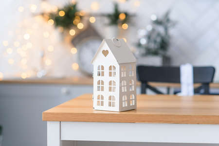 Cute little decorative house at backdrop of cozy Christmas lights. Winter holidays concept.