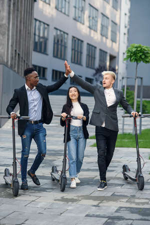 Confident multiracial office colleagues discussing business project go near office building with electric scooters