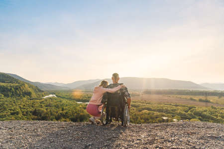 Beautiful woman hugs her disabled husband in wheelchair on a mountain hill at sunset. 免版税图像