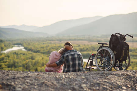 Pretty woman and her incapacitated husband resting together near his wheelchair on the hill.
