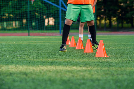 Close up soccer players legs running among plastic orange cones that standing on artificial stadium during workout.