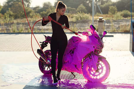 Beautiful pretty girl in tight-fitting seductive suit washes a motorcycle at self-service car wash service.