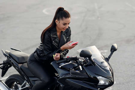 Beautiful female biker uses smartphone while sitting on stylish sport motorcycle at outdoors parking.