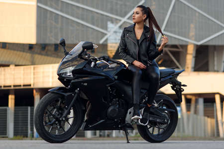 Attractive girl with long hair in black leather jacket and pants on outdoors parking with stylish sports motorcycle at sunset. 免版税图像