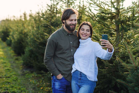 Happy bearded man and his pretty girlfriend making selfie photo at Christmas tree plantation, preparing for the holidays