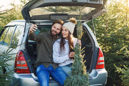 Joyful bearded man and pretty woman making selfie photo sitting in car trunk with fir tree at plantation area.
