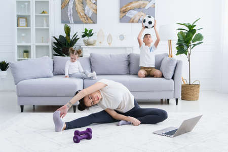 Mother stretching exercises while active energetic children playing on background. Mom doing yoga exercise at home.