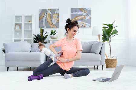 Young adorable mom making stretching exercises and practicing yoga with baby girl at home. Healthcare and sports concept