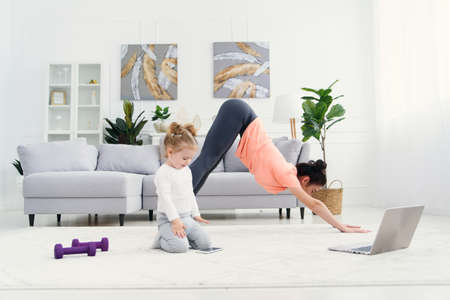 Young adorable mom makes stretching exercises and practicing yoga with baby girl at home. Health care and sports concept