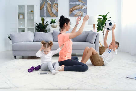 Sports mom with son doing morning work-out at home. Mum and son do exercises together, healthy family lifestyle concept