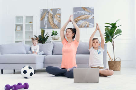 Mom and son practice yoga with laptop at home. Mother with child exercising in the morning. Healthy lifestyle concept.