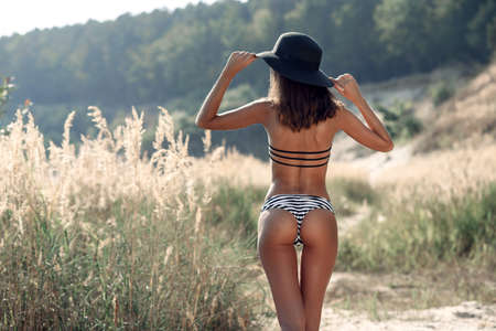 An attractive sporty girl in a bikini and black hat walking path to the beach. Beautiful fitness girl with perfect proportions. Summer vacation concept. Unrecognizable girl on the seashore.