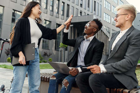 ultiracial men sitting on bench in front of office building and greeting with their female asian colleague with high five.