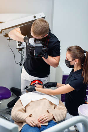 Dentist with assistant takes an intraoral photo of female patients teeth which sitting in the dental chair.
