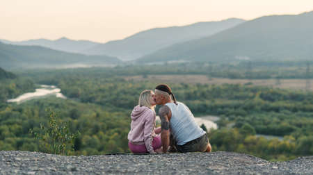 Young man hugs his girlfriend on the mountain peak at sunset background.