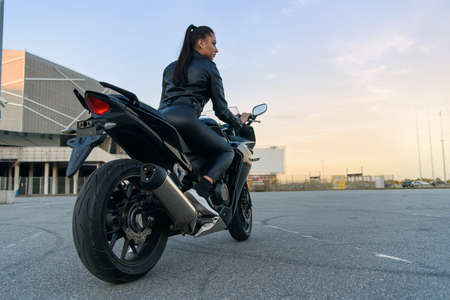 Back view of beautiful young woman in black leather jacket and pants on outdoors parking rides on stylish sports motorcycle at sunset. 版權商用圖片