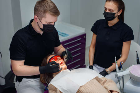 Beautiful female patient in red protective glasses in a dental chair at modern stylish clinic.