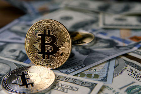 Bitcoin coins on US dollar banknotes. Cryptocurrency business concept. Exchange bitcoin cash for a dollar. 版權商用圖片