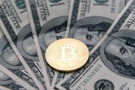 Golden Bitcoin coin on USD banknotes of one hundred dollar. Cryptocurrency business concept. Virtual money. 版權商用圖片