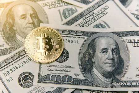 Bitcoin on USD banknotes of one hundred dollar. Virtual money investment. Cryptocurrency business concept. 版權商用圖片