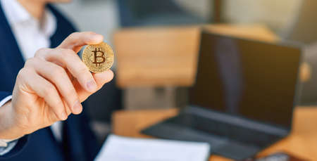 Successful businessman holds a gold bitcoin coin in his hand. Cryptocurrency business concept. Electronic virtual money investment. Cryptocurrency maining. 版權商用圖片