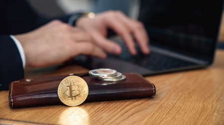 Businessman works on a laptop in his workplace. Cryptocurrency business concept. Electronic virtual money investment. Bitcoin, Litecoin, Ethereum coins on wallet. Exchange bitcoin cash for a dollar.