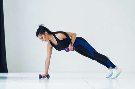 Young beautiful woman doing exercises with dumbbells in fitness studio. Athletic girl enjoying her training process.