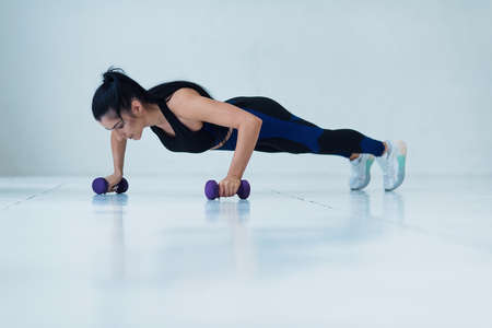 Young muscular woman doing push-up exercise with dumbell on hard workout at the gym.