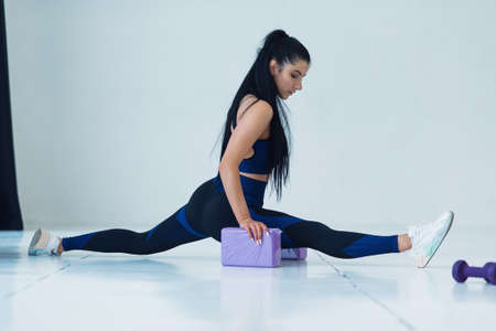 Caucasian fit trainer practice twine method during morning warm up enjoying healthy lifestyle and calmness, experienced woman in tracksuit stretching flexible muscles during mat workout outdoors