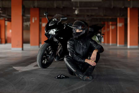 Stylish young woman motorcycle rider with beautiful eyes in black protective gear and full-face helmet near her bike on underground parking.