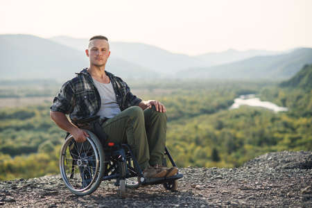 Portrait of young strong-willed motivated man in a wheelchair enjoying the beauty of nature in the mountains.