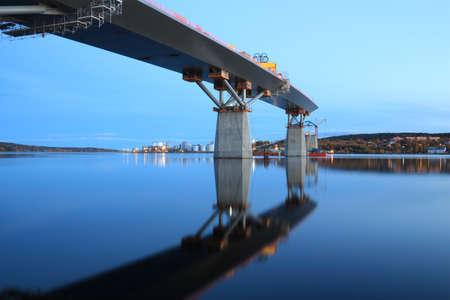 Nightfall, bridge construction reaching over water, view from beneath  Sundsvall, Sweden photo