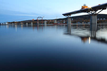 Nightfall, bridge construction reaching over water, view from beneath  Sundsvall, Sweden photo