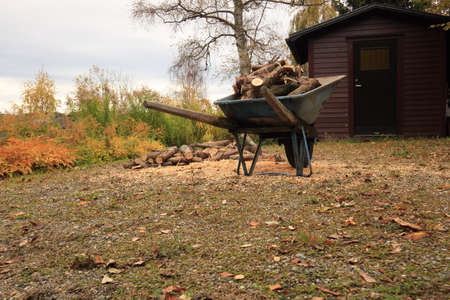 wheelbarrow loaded with firewood in autumn, Town of Tmraa, Sweden Stock Photo - 23770122