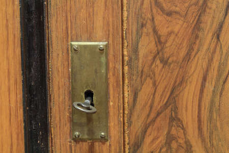 graining: key in a keyhole on an old door with patina