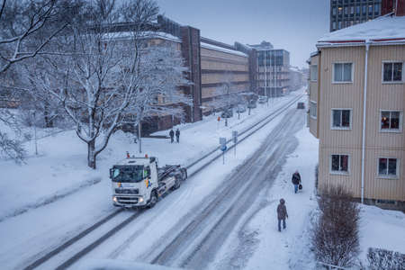 Truck driving down town town when it is snowing and people are headed in different directions as their aims are different Sundsvall, Medelpad Sweden,  02 2013 photo