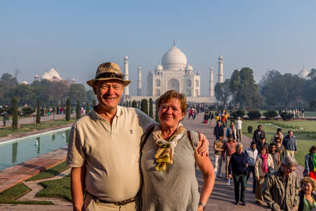 Adult couple posing in front of the Taj Mahal anxious to see one of the seven wonders a world heritage building symbolising loveAgra, Uttar Pradesh India   02 2013