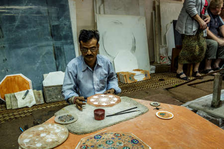 descendants: Marble worker outside a marble shop fitting semiprecious stones in patterns of marble products, this workers are said to be descendants of those who once built the Taj MahalAgra, Uttar Pradesh India   02 2013 Editorial