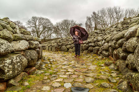 humilde: Señora madura con paraguas caminando en un mojón Foto de archivo