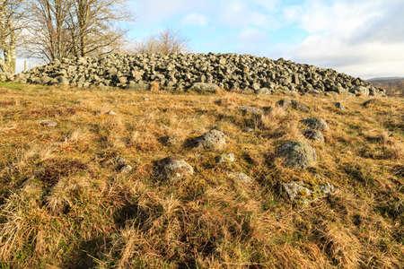 humilde: Un mojón en Ekornavallen, Suecia en un campo con diferentes tipos de tumbas antiguas