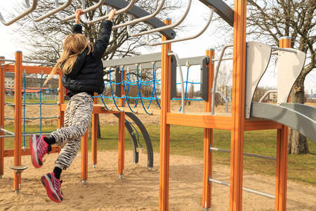 tog: Young girl plays acrobatically on a public municipality playground Stock Photo