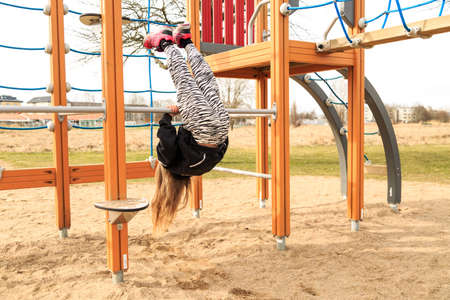 lithe: Young girl plays acrobatically on a public municipality playground Stock Photo