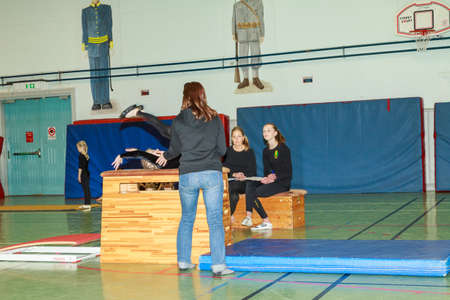 tog: Oerebro, Sweden - May 3, 2015: Young girls playing and competeing in gymnastics in a former military hall to get some routine in competing