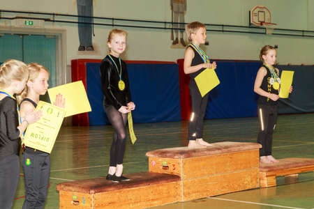 trait: Oerebro, Sweden - May 3, 2015: Young girls playing and competeing in gymnastics in a former military hall to get some routine in competing