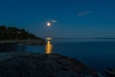 mirk: Nightfall over the island with the moon reflecting its beams on the Baltic sea surface Stock Photo